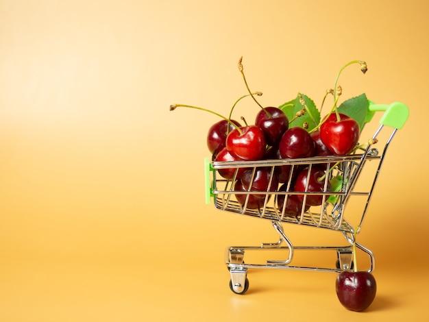 オレンジ色の背景に熟した赤いサクランボでいっぱいのスーパーマーケットのカート。