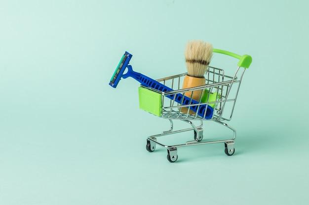 シェービング用品でいっぱいのスーパーマーケットのカート。男性の顔のケアのために設定します。