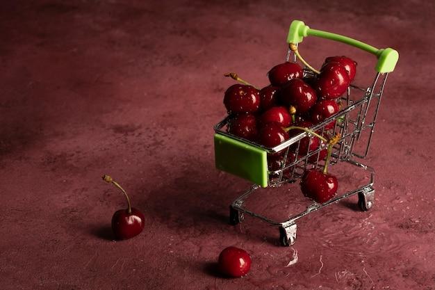 슈퍼마켓 카트는 빨간 배경에 잘 익은 빨간 체리로 가득 차 있습니다.