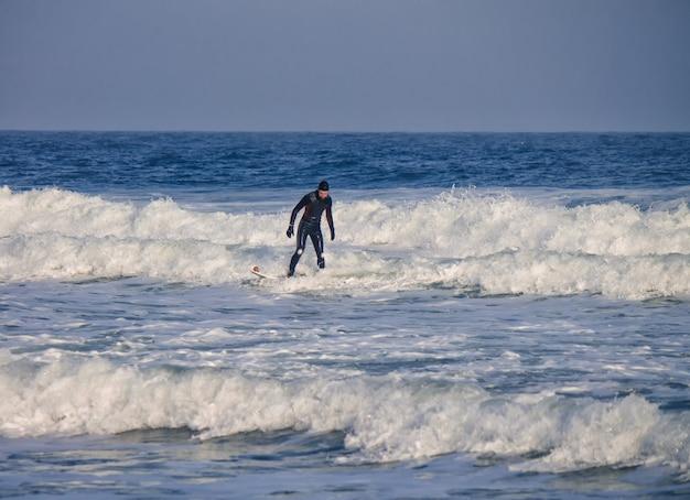 Серфер катается на волнах в воде в гидрокостюме. всплеск волны. водонепроницаемый костюм