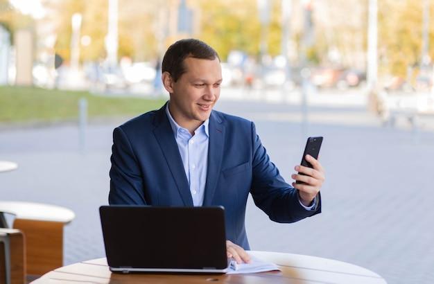 Удивленный бизнесмен сидит за столиком в кафе на улице, работает по мобильному телефону в деловом районе города. рядом ноутбук.