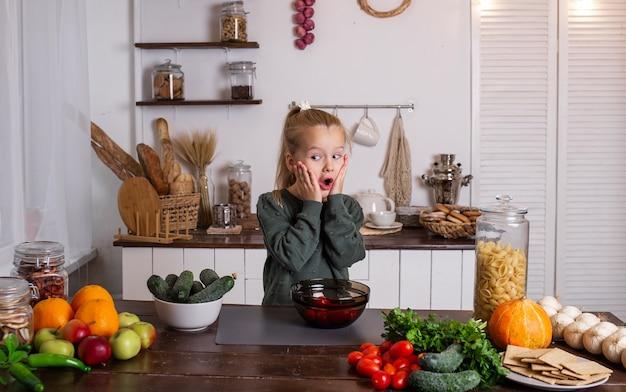 놀란 어린 금발 소녀가 과일과 야채가 있는 테이블에 앉아 있다