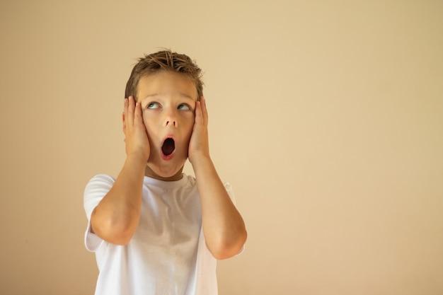 Удивленный или испуганный мальчик 7-10 лет в белой футболке стоит и кричит, положив руки на щеки на бежевом фоне. скопируйте пространство.