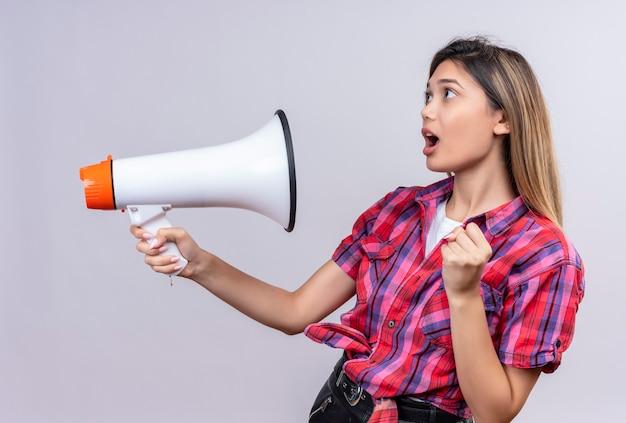 Удивленная симпатичная молодая женщина в клетчатой рубашке с мегафоном