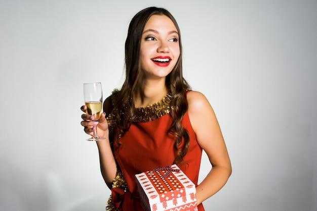 Удивленная молодая девушка в красном платье и с золотой мишурой на шее празднует новый 2018 год с бокалом шампанского