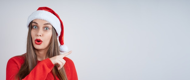 赤いセーターを着たサンタの帽子をかぶった驚いた若い女性が、人差し指を横に向けます。広告用のコピースペース付きバナー。