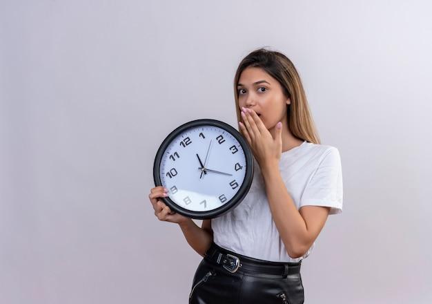 見て、口に手を保ちながら壁時計を保持している白いtシャツに驚いた若い女性