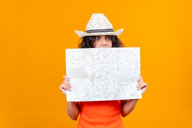 Удивленная молодая женщина с короткими волосами в оранжевой рубашке в шляпе от солнца просматривает карту