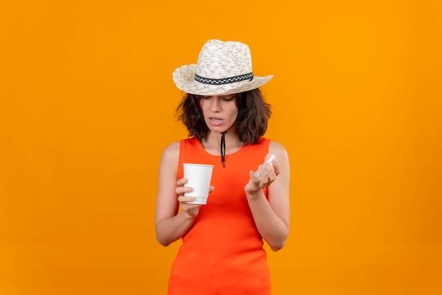 플라스틱 컵을 여는 태양 모자를 쓰고 주황색 셔츠에 짧은 머리를 가진 놀란 젊은 여자