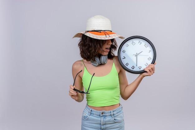 Удивленная молодая женщина с короткими волосами в зеленом топе в шляпе от солнца смотрит на настенные часы и держит солнцезащитные очки на белом фоне