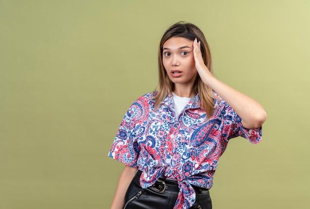 머리에 손을 유지 페이즐리 인쇄 셔츠를 입고 놀라운 아름다운 젊은 여자