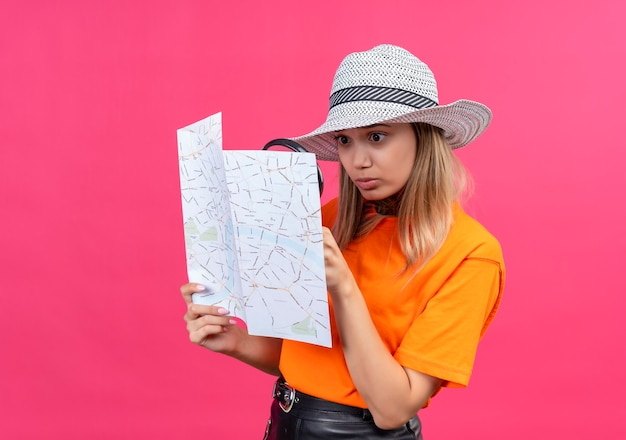 虫眼鏡で地図を見て日よけ帽をかぶったオレンジ色のtシャツを着た驚くべきかなり若い女性
