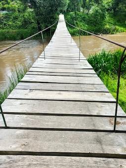 緑の森の真ん中にある、川に架かる吊り下げられた木製の歩道橋。