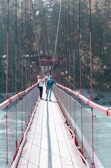 Подвесной мост через широкую реку в горах. безопасный переход моста с одного берега на другой.
