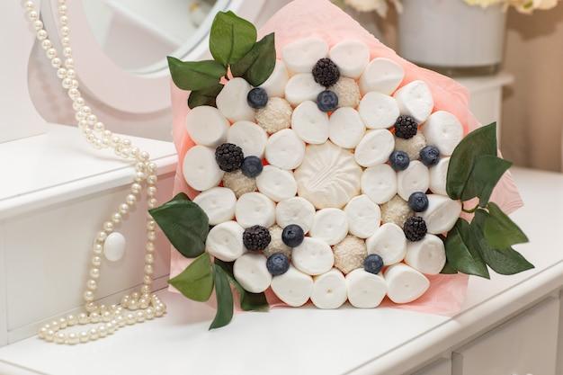 マシュマロとベリーの甘い花束がテーブルの上にあります
