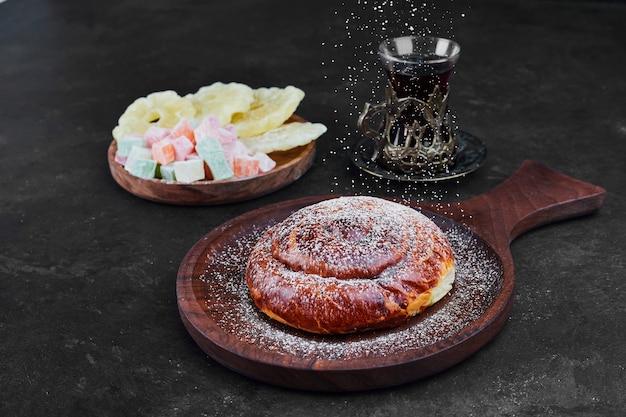 Сладкая булочка с сухофруктами и стакан чая. фото высокого качества