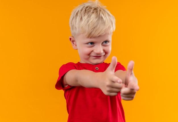 Милый милый маленький мальчик со светлыми волосами и голубыми глазами в красной футболке, указывая указательными пальцами