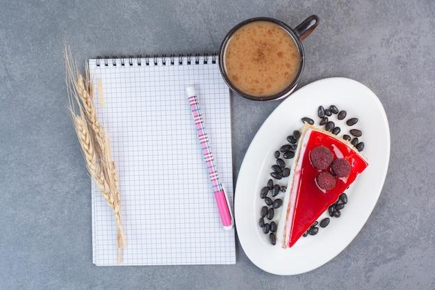 Сладкий вкусный кусок торта с листом бумаги на сером столе.