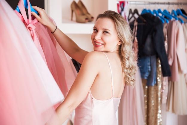 Милая девушка со светлыми волосами и розовой пижамой держит юбку из своего гардероба. девушка улыбается и смотрит в камеру.