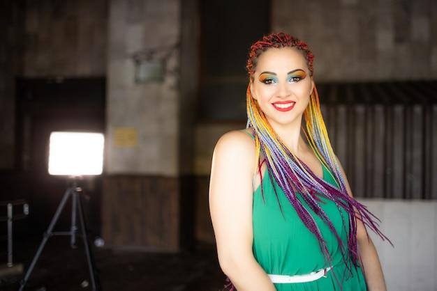 Милая девочка с очень яркими тенями и блестками с переливающимися африканскими косичками в светло-зеленом платье. милые улыбки гуляют по улицам города, наслаждаясь теплом наступающей весны.