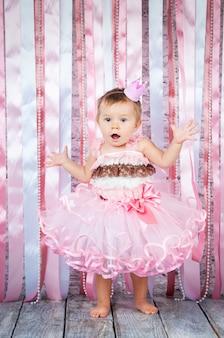 왕관을 쓴 달콤한 소녀와 아름다운 분홍색 드레스가 무대에서 손을 들고 있습니다.