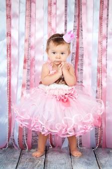 Милая маленькая девочка в короне и красивом розовом платье поднимает руки