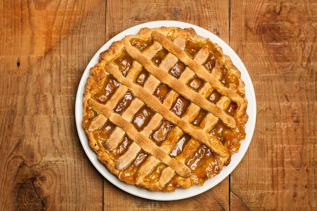 보기 바로 위의 나무 테이블에 하얀 접시에 고구마 파이