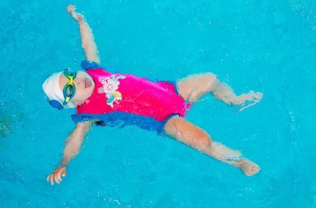 水泳の先生は子供にプールで泳ぐように教えます