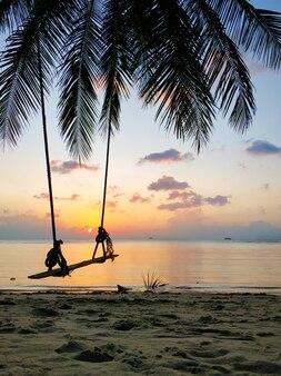 Качели висят на пальме на тропическом песчаном пляже у океана. закат на пляже.