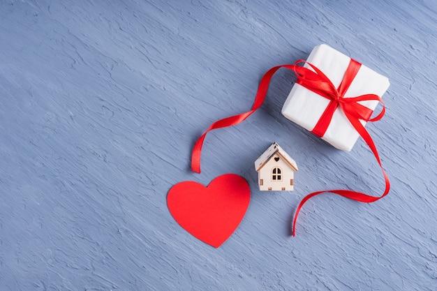 사랑, 가족, 관계의 상징. 빨간 리본이 달린 흰 종이에 선물