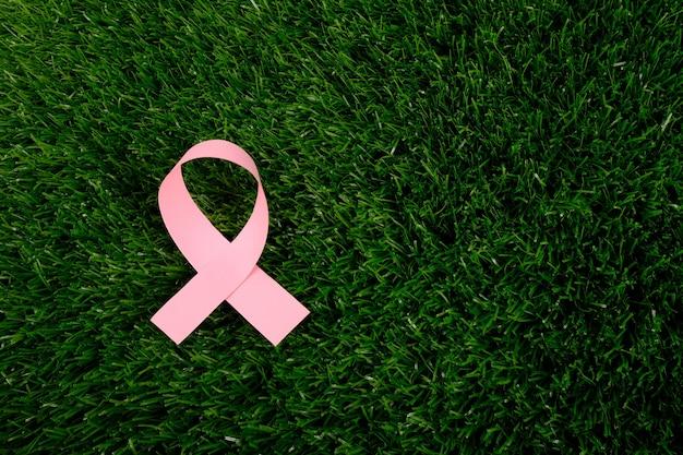 緑の芝生のコピースペースでの癌との闘いのシンボル。