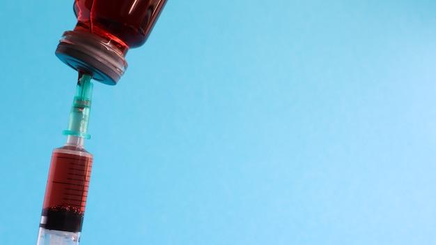 赤い液体ボトルから注射器が突き出ています。青色の背景に分離されました。