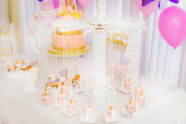 Стол, накрытый белой скатертью, на которой разложены различные сладости, деревянная белая карусель с мини-пирожными на переднем плане.