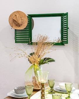 花瓶に皿、グラス、装飾花を添えたテーブル。鏡と麦わら帽子のダイニングルーム。