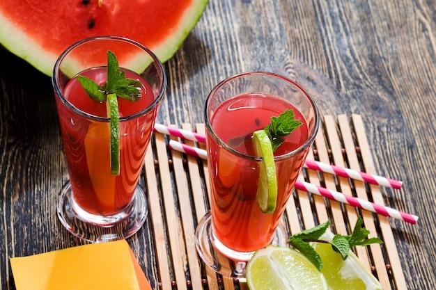 Стол с едой и красными спелыми арбузами, из которых делается вкусный и полезный арбузный сок.