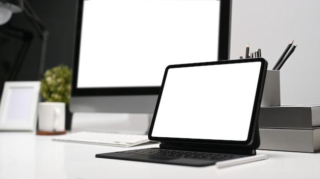 Планшетный компьютер с корпусом клавиатуры и компьютером на современной рабочей станции. пустой экран для монтажа графического дисплея.
