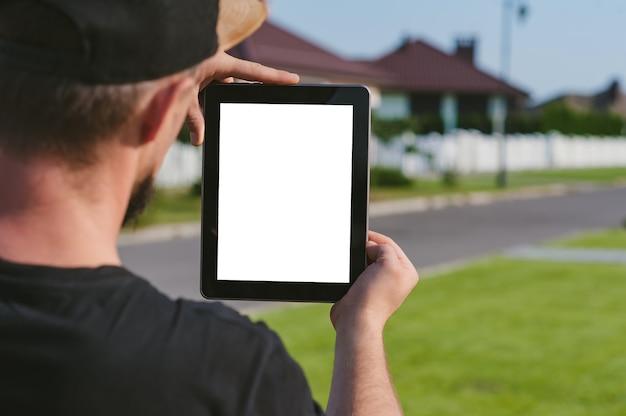 家を背景に、男の手にタブレット。