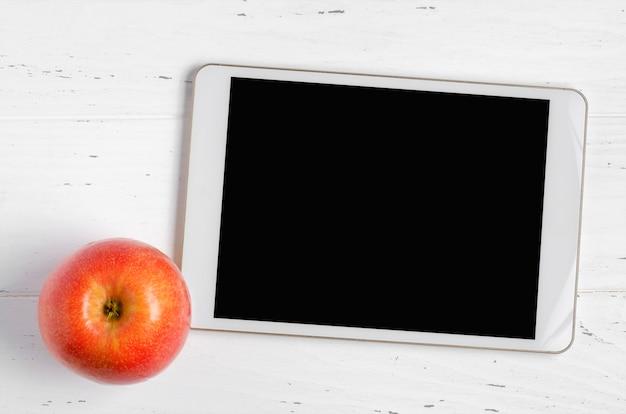 빈 화면 및 흰색 나무 바탕에 애플 태블릿. 학교 어린이 또는 온라인 학습을위한 개념 앱. 공간을 복사하십시오.