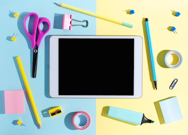 Планшет с пустым экраном и канцелярские товары на цветном фоне. концепция приложения для школьников или онлайн-обучения для детей. копировать пространство