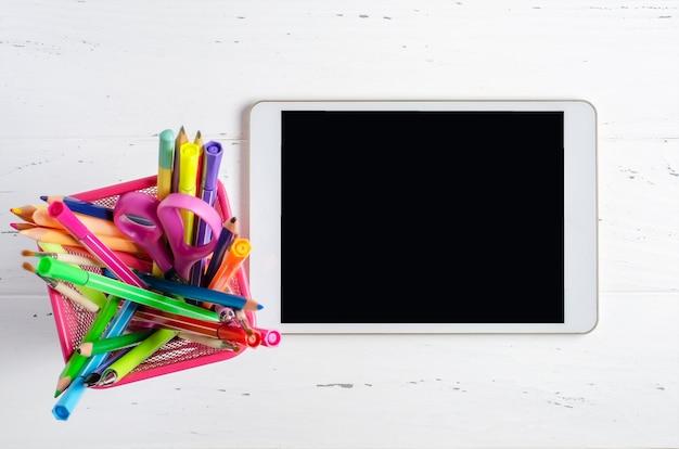 空の画面と白い木製の背景に事務用品を備えたタブレット。学童やオンライン学習のためのコンセプトアプリ。スペースをコピーします。