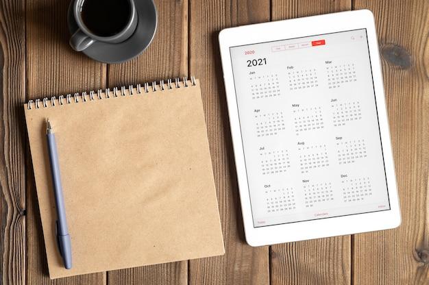 2021年のオープンカレンダー、一杯のコーヒー、木の板のテーブルの背景にクラフト紙のノートブックとタブレット