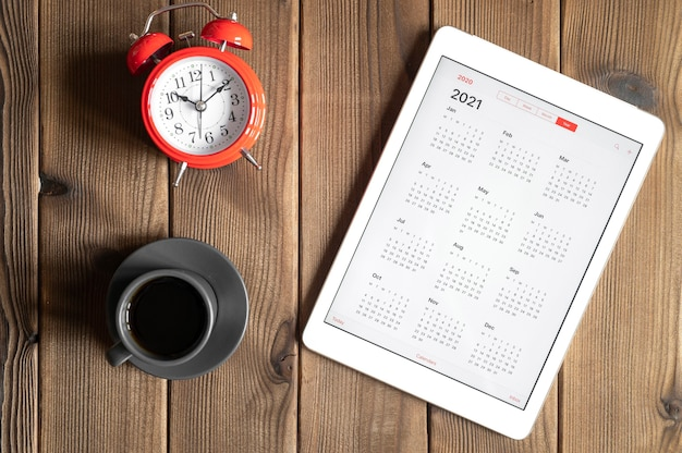 2021年のオープンカレンダー、一杯のコーヒー、木の板のテーブルの背景に赤い目覚まし時計が付いたタブレット