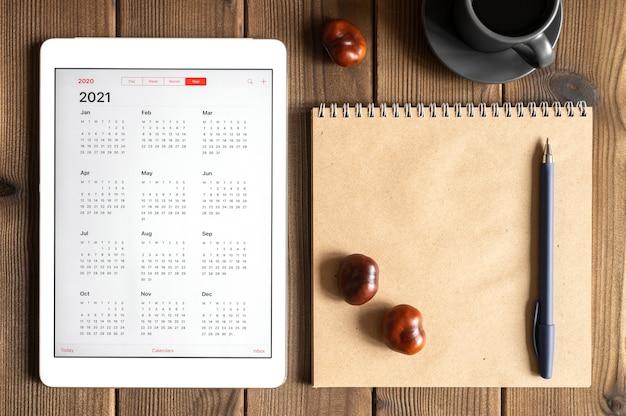 2021年のオープンカレンダー、一杯のコーヒー、栗、木の板のテーブルの背景にクラフト紙のノートブックとタブレット