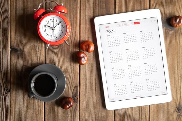 2021年のオープンカレンダー、一杯のコーヒー、栗、木の板のテーブルの背景に赤い目覚まし時計とタブレット