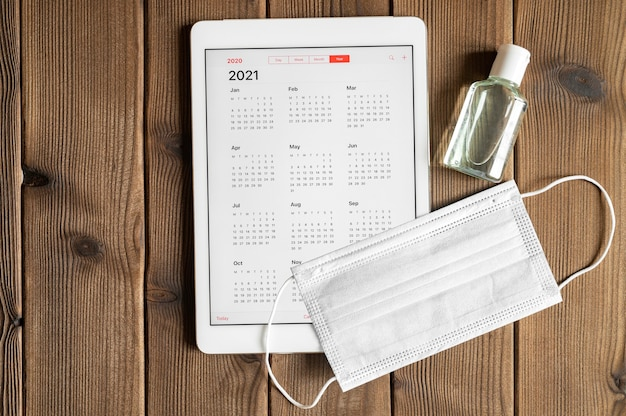 Таблетка с открытым календарем на 2021 год и защитной медицинской маской и дезинфицирующим средством для рук на фоне стола из деревянных досок. концепция защиты от коронавируса covid-19 в 2021 году.