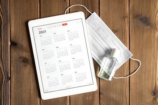2021年のオープンカレンダーと木の板のテーブルの背景に保護医療マスクと手指消毒剤を備えたタブレット。 2021年のcovid-19コロナウイルス保護コンセプト