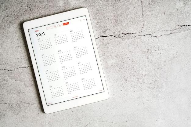 灰色のコンクリートのテーブルの上に2021年のオープンカレンダーを持つタブレット
