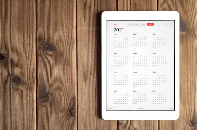 木の板のテーブルの背景に2021年のオープンカレンダーを持つタブレット。テキスト用のスペース