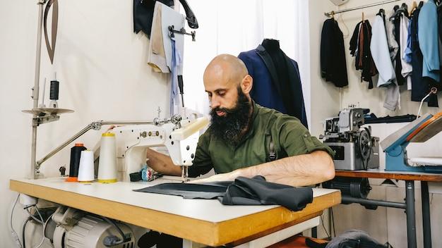 Портной в швейной мастерской за работой. его студия солнечная. видны цветные ткани, одежда.