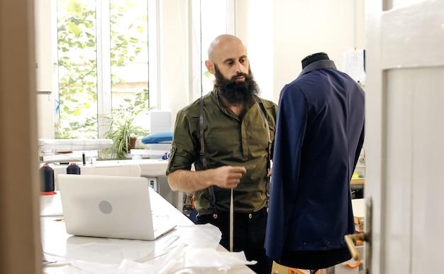 仕事中の縫製工場の仕立て屋。彼のスタジオは晴れです。色のついた生地、衣服が見えます。
